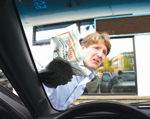 An unnamed homeless man cleans windshields with copies of The Pirate & Yesterday outside a local convenience store.