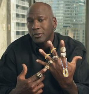 "Michael Jordan was photographed showing off his latest ""unbeatable"" ring collection of six NBA championship rings, two wedding rings and something on a chain he won in a poker game from ""some short Baggins dude with big furry feet."""
